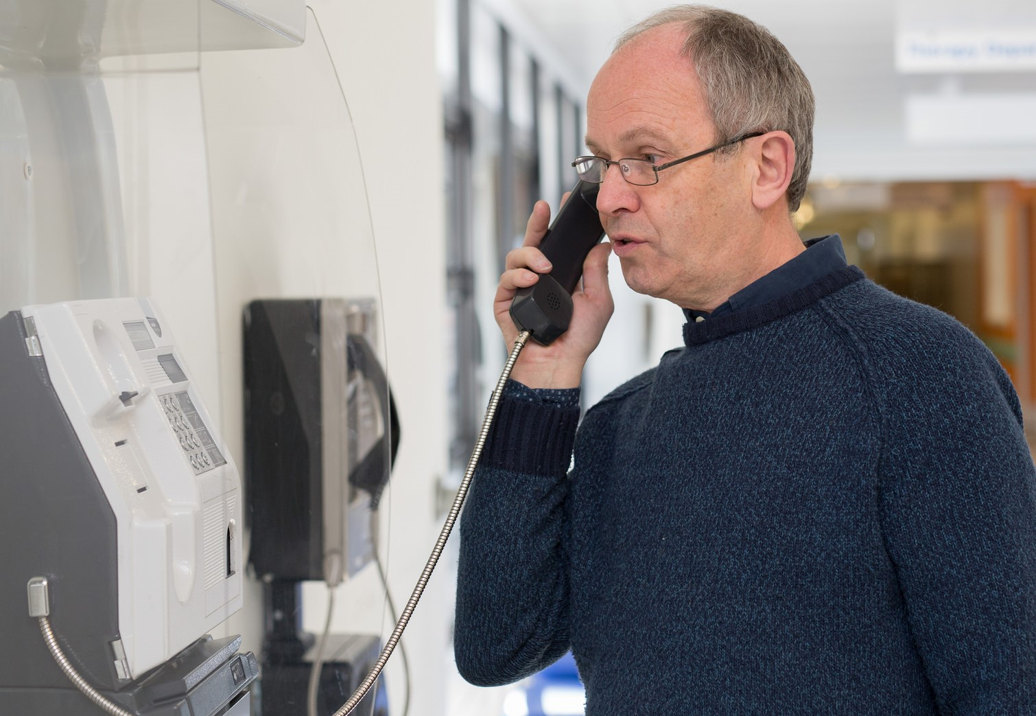 Man using wall mounted public phone