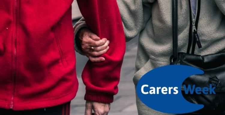 Image shows two elderly people walking together. The woman is holding the man's arm. The Carers Week logo is in the corner.