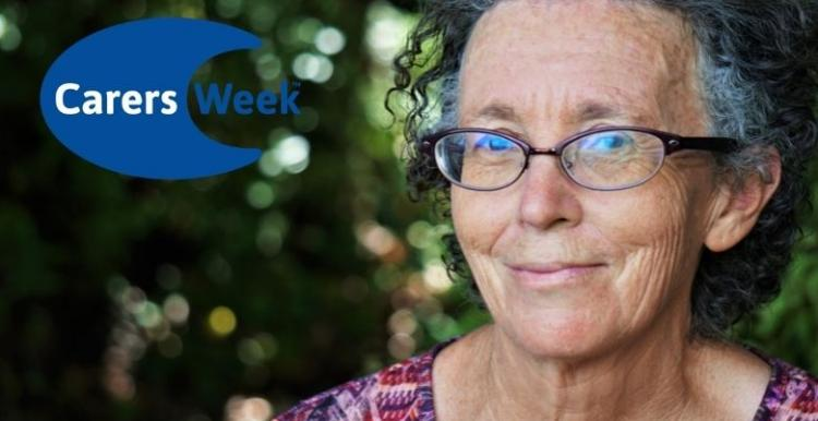 A woman wearing glasses is looking into the camera lens and smiling with a closed mouth. Logo in the corner says Carers Week.
