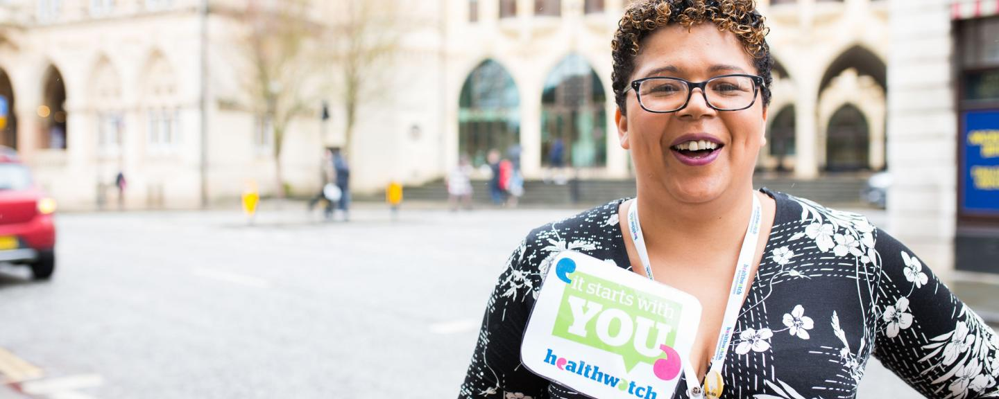 Healthwatch staff member holds an It Starts With You sign to promote giving views