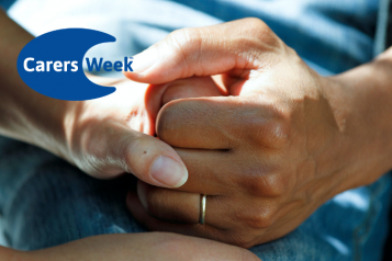 Two people's hands clasped together to provide comfort. Logo for Carers Week in the top left corner.