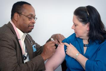 Doctor giving injection to a lady patient