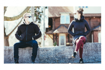 Picture of man and woman sitting apart from each other on a wall and wearing face masks