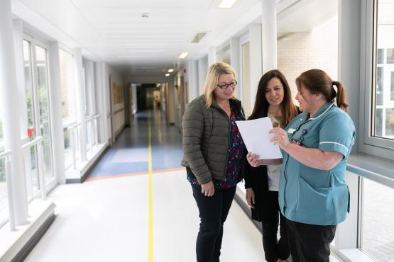 Two olunteers on hospital visit talking to nurse