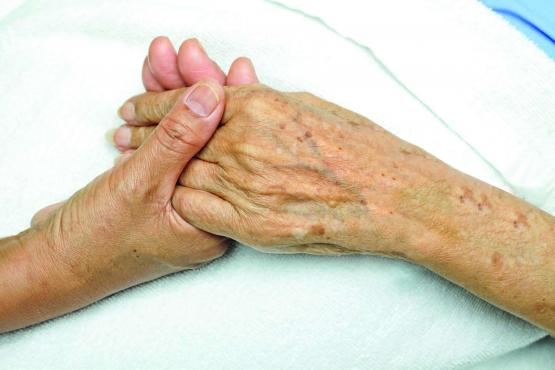 Two people holding hands in a suportive way