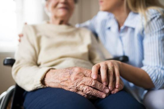 Older woman sitting in wheelchair with carer holding hand