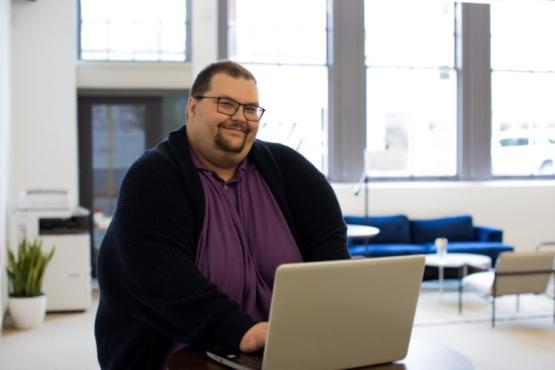 Smiling man seated and using a laptop