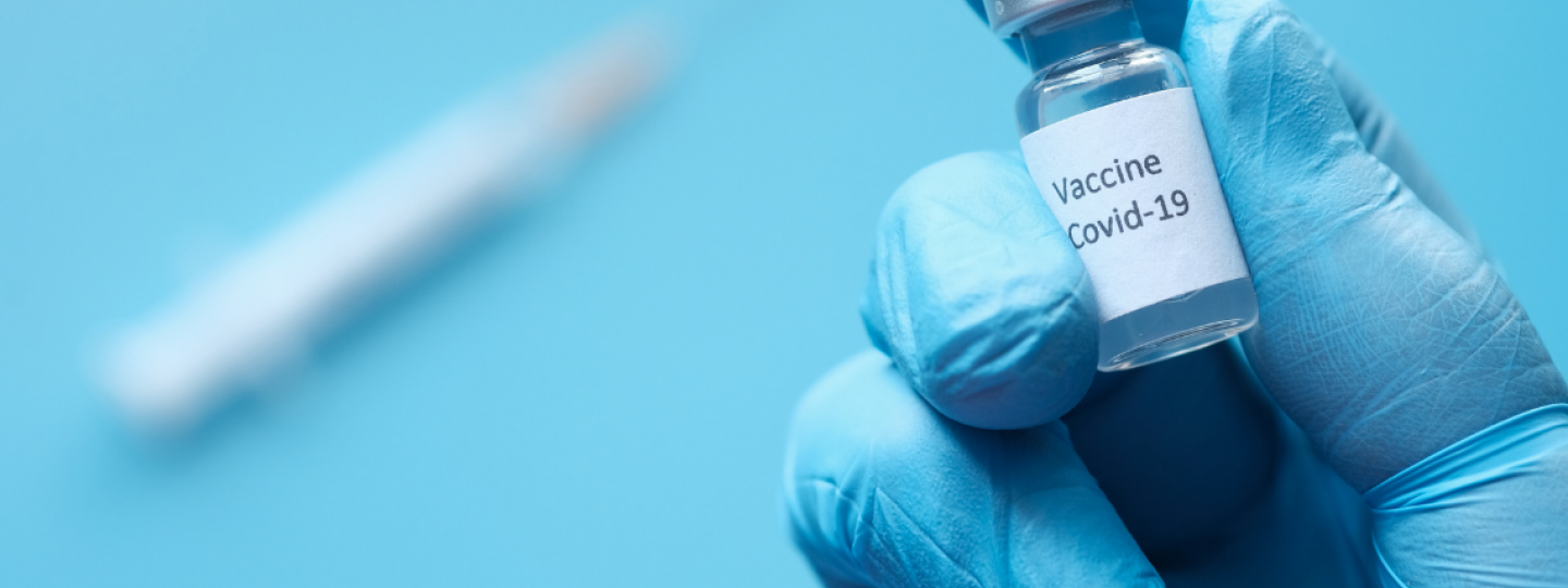 Image of hand holding bottle of COVID-19 vaccine