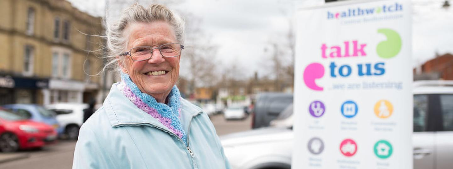 Lady standing in front of Healthwatch Talk to us banner