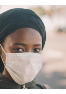 Young black woman staring into the camera lens. She is wearing a face mask.